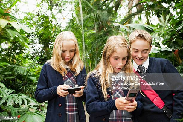 kids in school uniforms with cell phones - compassionate eye foundation stock pictures, royalty-free photos & images