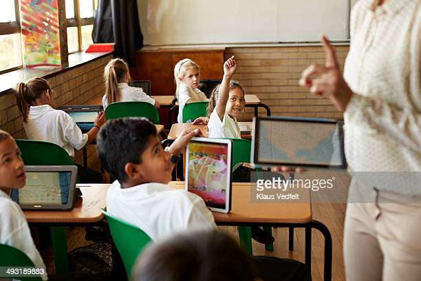 Kids in schoolclass getting taught with tablets