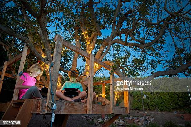 kids in treehouse with digital tablets
