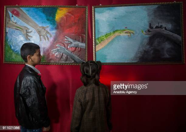Kids inspect the paintings of Syrian painters Fatima Ahmed and Hikmet Ismael during an art exhibition which is on Syrian people's experience, natural...
