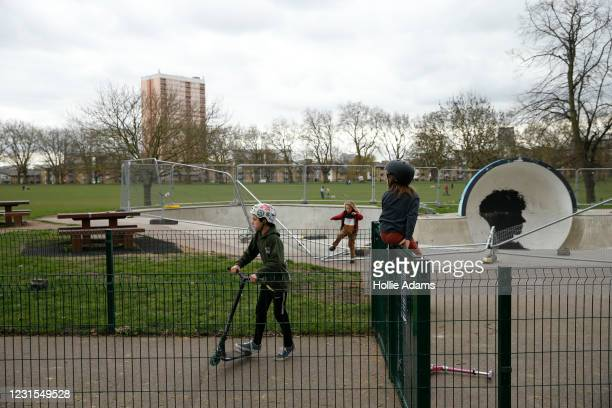 Kids jump the fence at the Victoria Park skatepark on March 6, 2021 in London, England. Londoners are enjoying bright weather as end of lockdown...