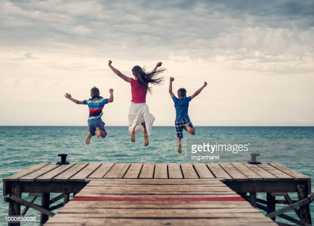 Kids jumping from pier into the sea