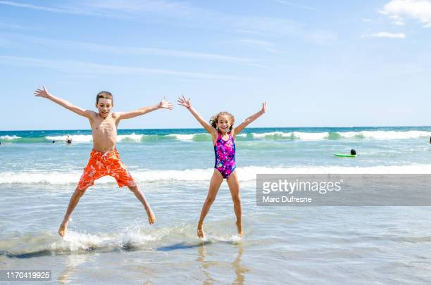 kids jumping in the air at the beach - atlantic city stock pictures, royalty-free photos & images