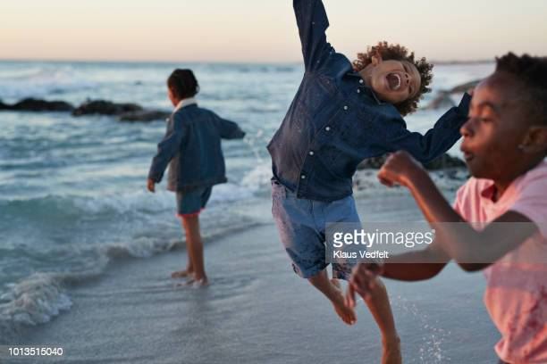 kids jumping in the water's edge at sunset - 感動 ストックフォトと画像