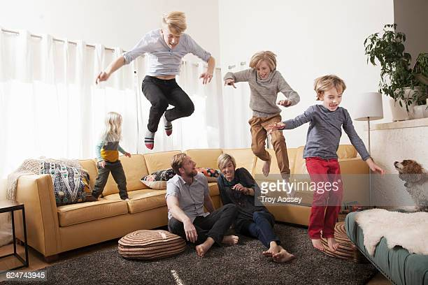 Kids jumping off couch over parents.