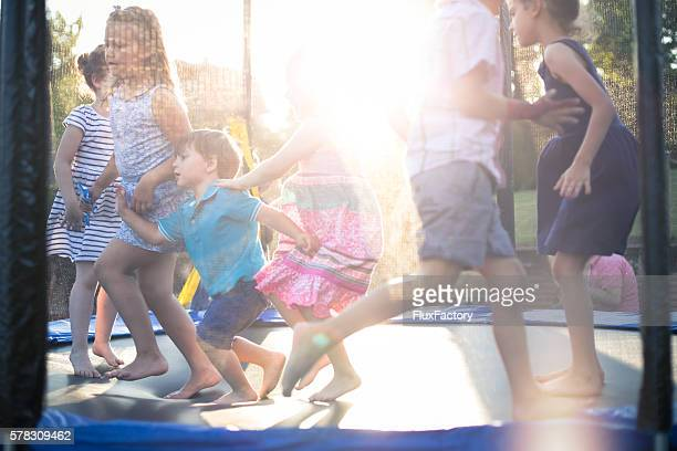 kids jumping on a trampoline and having a party