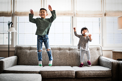 kids jumping on couch at home - gettyimageskorea
