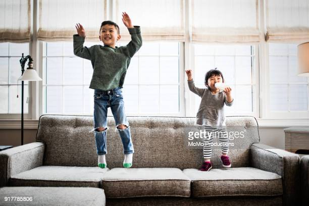 kids jumping on couch at home - asian drink stock photos and pictures