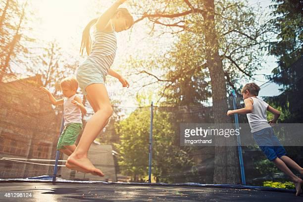 Kinder springen auf Trampolin-Garten