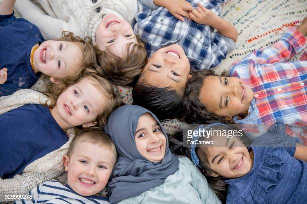 kids laying in a circle - migrant children stock photos and pictures