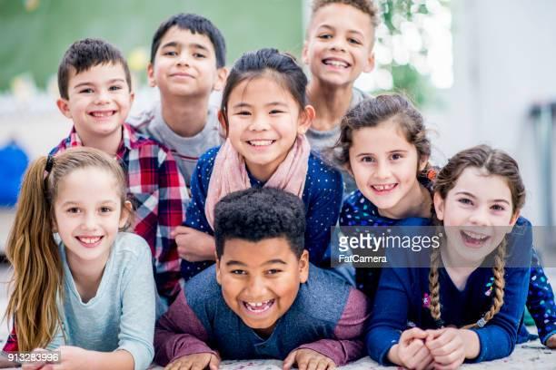 bambini sdraiati sul pavimento - foto di classe foto e immagini stock
