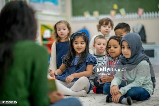 kids listening to a story - migrant children stock photos and pictures