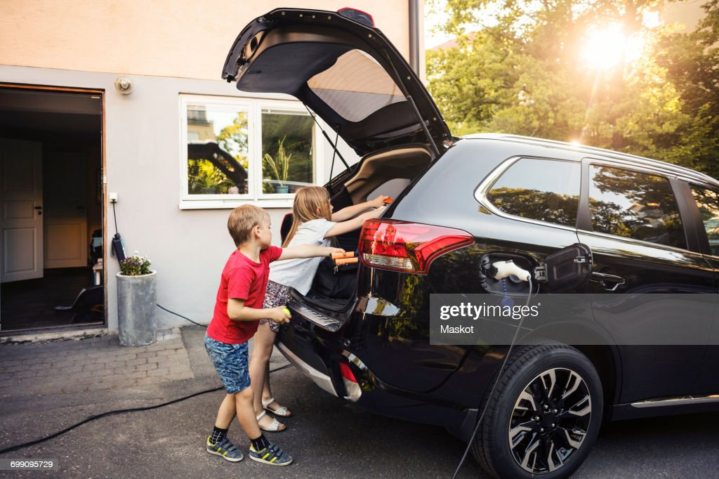 Kids loading black electric car trunk against house in back yard : Stock Photo