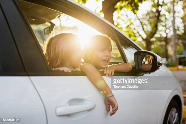 Kids look out from car window