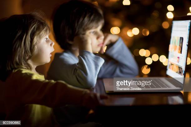 Kids looking a laptop in the dark
