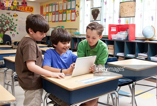 Kids looking at ipad / tablet in classroom