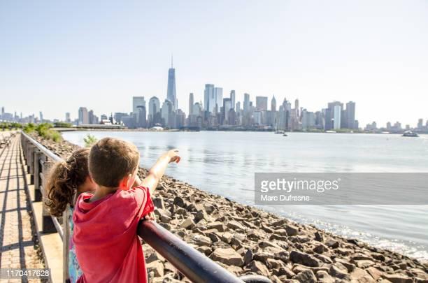miúdos que olham a skyline de manhattan do parque de estado da liberdade - new york state - fotografias e filmes do acervo
