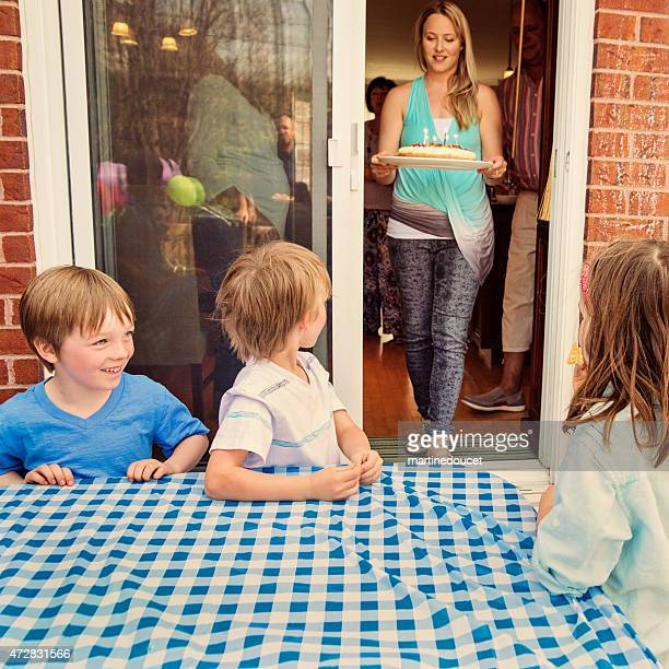 "kids looking at mom coming out with the birthday cake! - ""martine doucet"" or martinedoucet stock pictures, royalty-free photos & images"