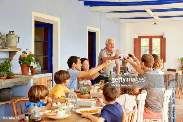 Kids looking at parents toasting glasses at table