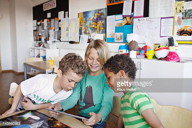 Kids looking at tablet in classroom