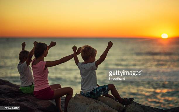 Kids looking at the sunset over the Italian sea.