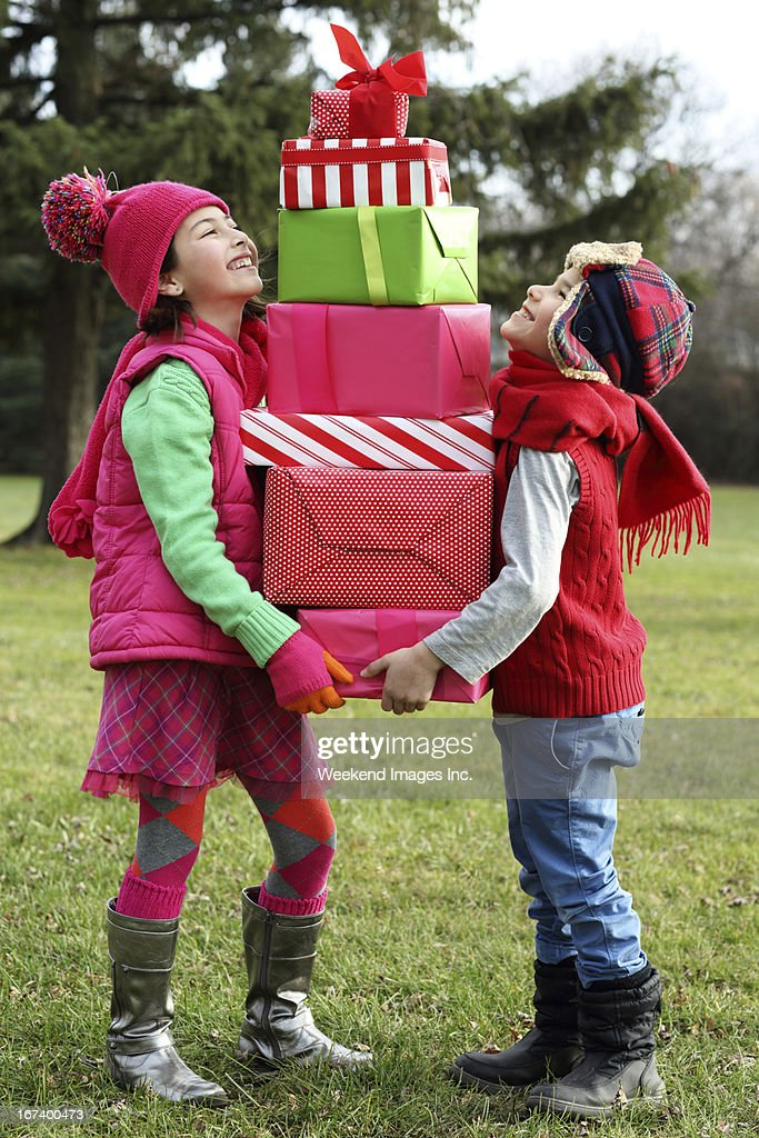 Kids looking on a little gift : Stock Photo