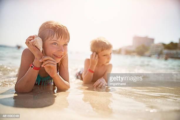 Kinder liegen am Strand lauschen Sie Muscheln