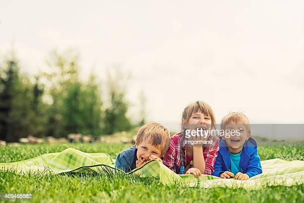 Kids lying on blanket in grass enjoying funny spring picnic.