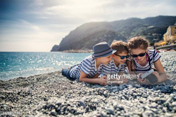 bambini sdraiati sulla spiaggia di ciottoli e che recensivano le foto sulla fotocamera - liguria foto e immagini stock