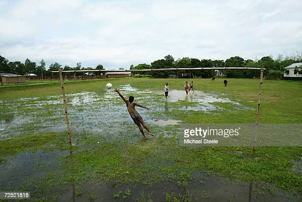 Kids make the most of wet conditions on their local village football field on October 10 2003 in Dhaka Bangladesh