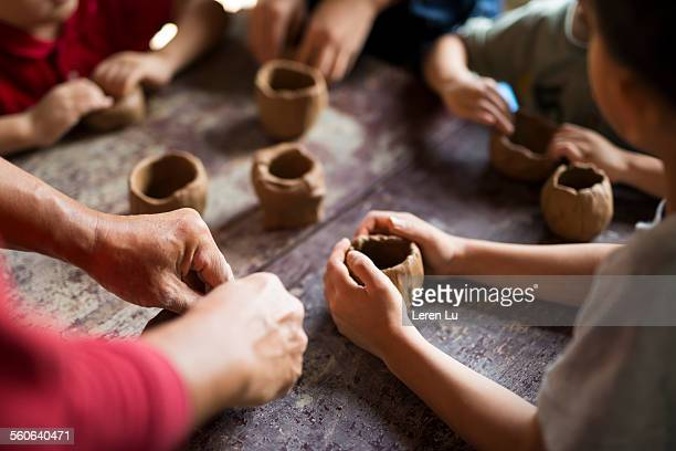 Kids making cups with pottery clay