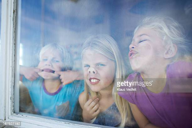 Kids making funny faces behind window