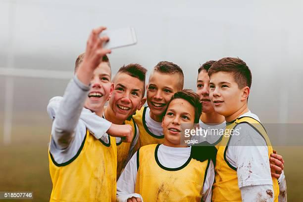 Niños haciendo autofoto después de jugar al fútbol.