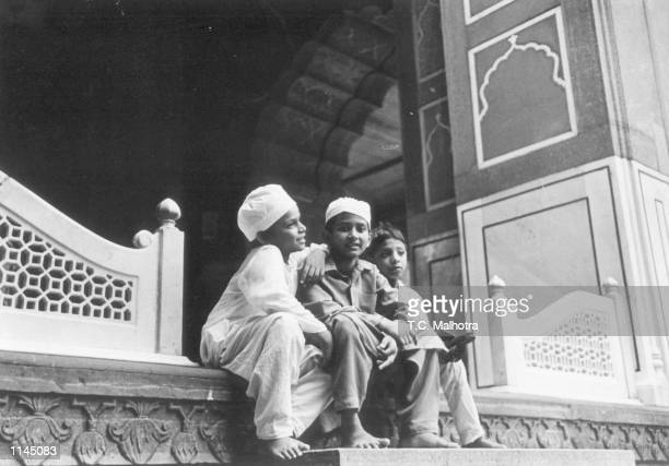 Kids of a muslim family sit on the steps of a traditional muslim house in Old Delhi India