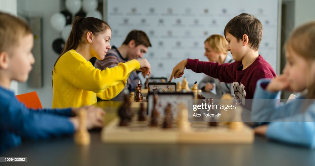 Kids of different ages, boys and girls, playing chess on the tournament in the chess club : Stock Photo