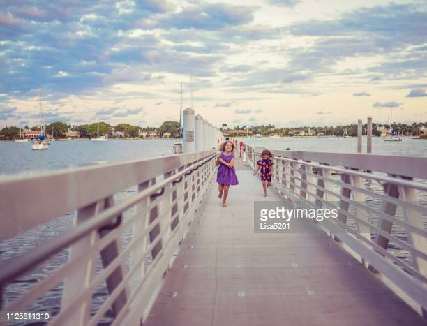 kids on a dock - west palm beach stock pictures, royalty-free photos & images