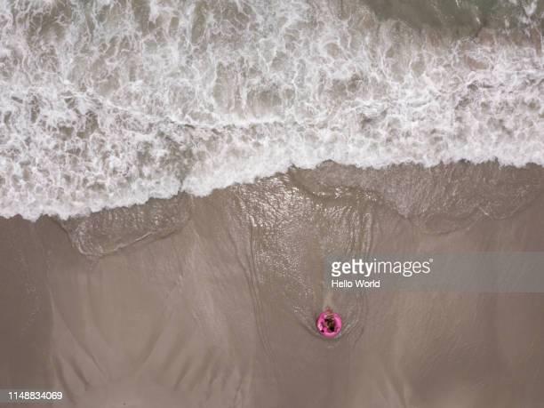 kids on a pink flamngo inflatable at waters edge on beach - waterlijn stockfoto's en -beelden
