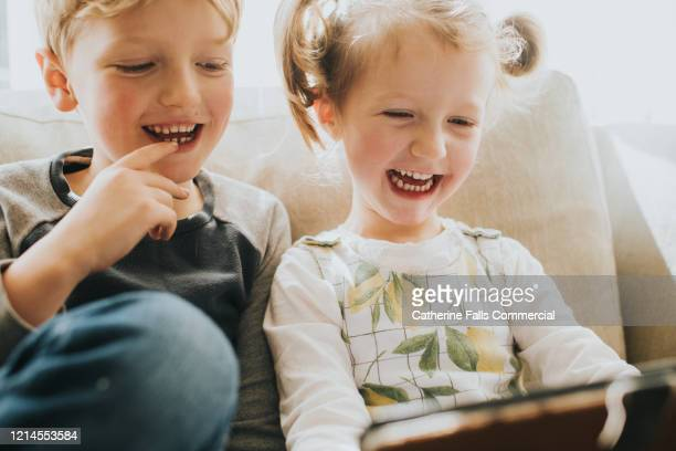 kids on a tablet - awe stock pictures, royalty-free photos & images
