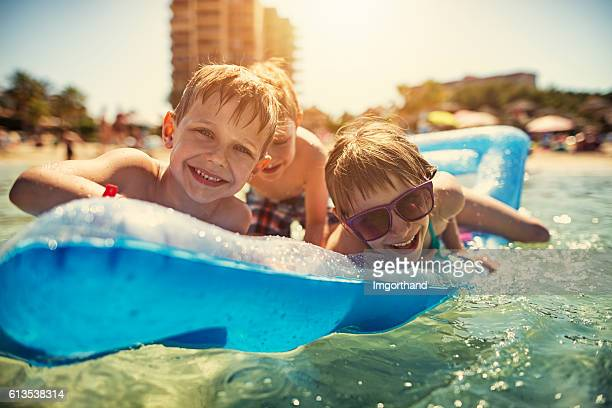 Kids on air mattress playing and laughing at sea