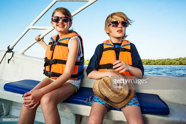 Kids on boat riding with life perservers