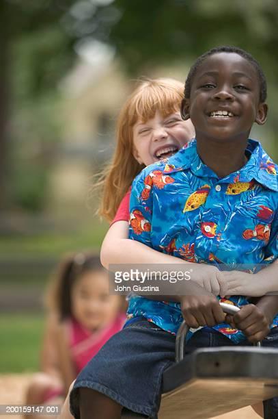 Kids (6-8) on seesaw in park, smiling, portrait