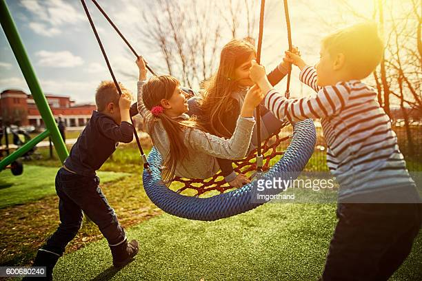 Kids on the playground, laughing and swinging on big swing
