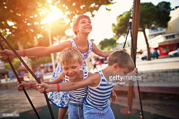 Kids on the playground, swinging on a big swing