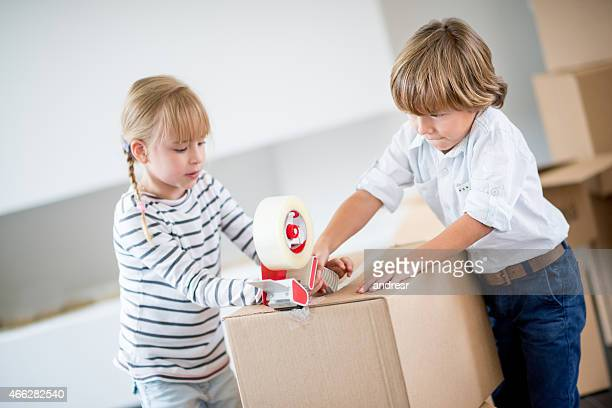 Kids packing and closing boxes with tape gun