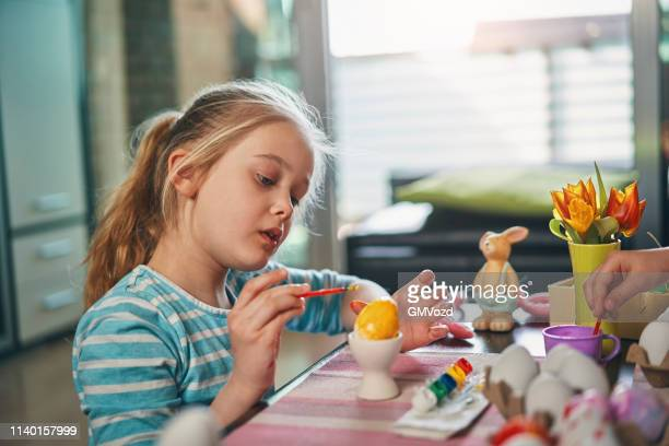 niños pintando huevos de pascua - abril fotografías e imágenes de stock