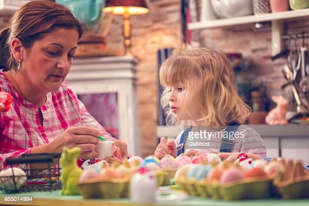 Kinder malen Ostereier.