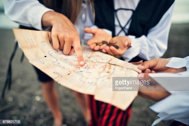 niños a piratas leyendo el mapa del tesoro en una playa - actividad fotografías e imágenes de stock
