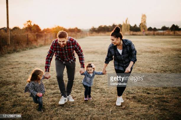 kids plaing in meadow with parents - life insurance stock pictures, royalty-free photos & images