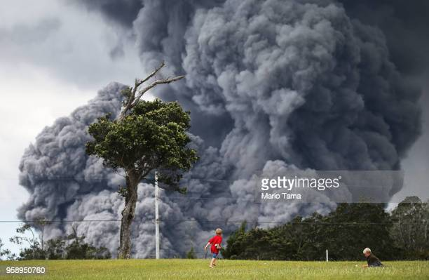 Kids play at a golf course as an ash plume rises in the distance from the Kilauea volcano on Hawaii's Big Island on May 15 2018 in Hawaii Volcanoes...