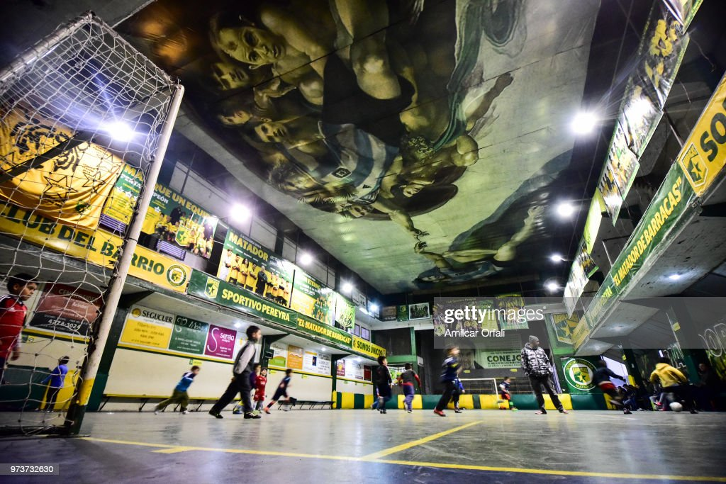Kids play at the 5-a-side pitch of Sportivo Pereyra de Barracas club on June 13, 2018 in Buenos Aires, Argentina. The mural was painted in the ceiling of the pitch by local artist Santiago Barbeito depiciting the 'Creation of Adam' and making a tribute to Argentine football stars.